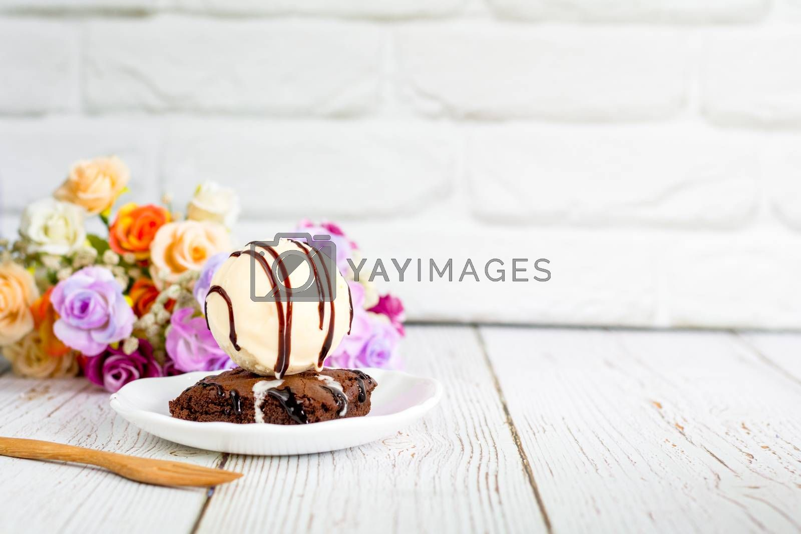 Piece of brownie cake with vanilla ice cream on white small plate on wooden table and with brick wall with copy space.