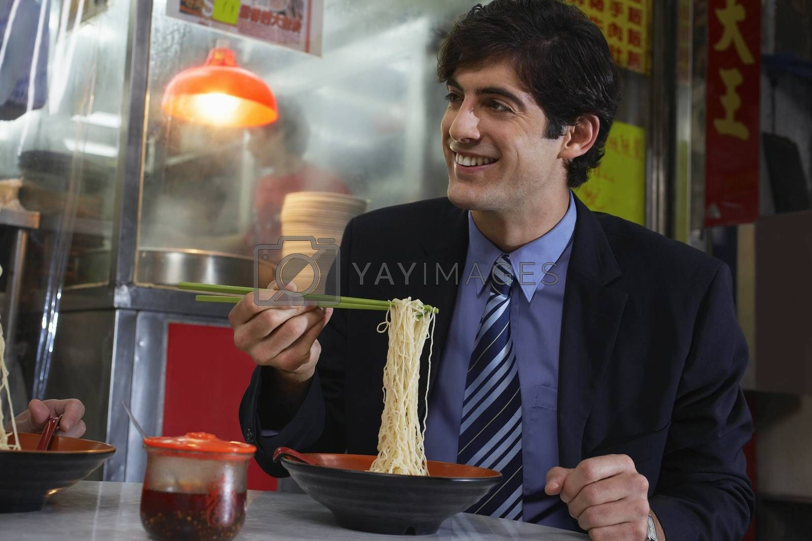 Young business man eating noodles in bar