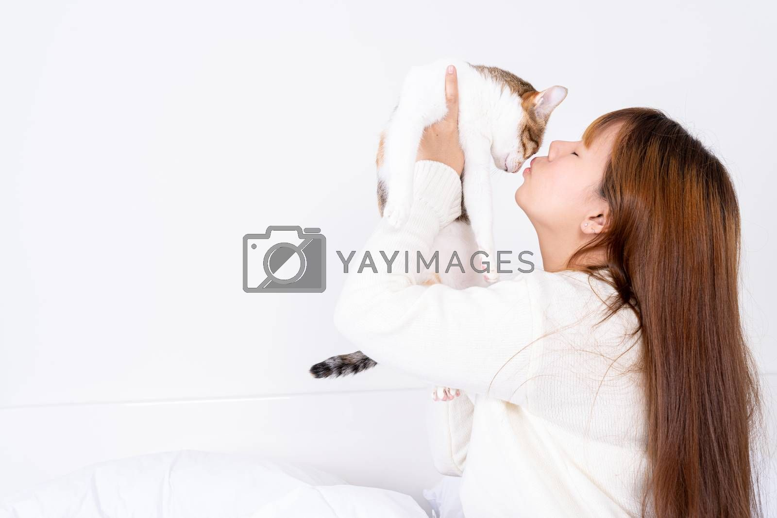 Woman at home holding and kissing her lovely fluffy cat. Multicolor tabby cute kitten. Pets and lifestyle concept. by mikesaran