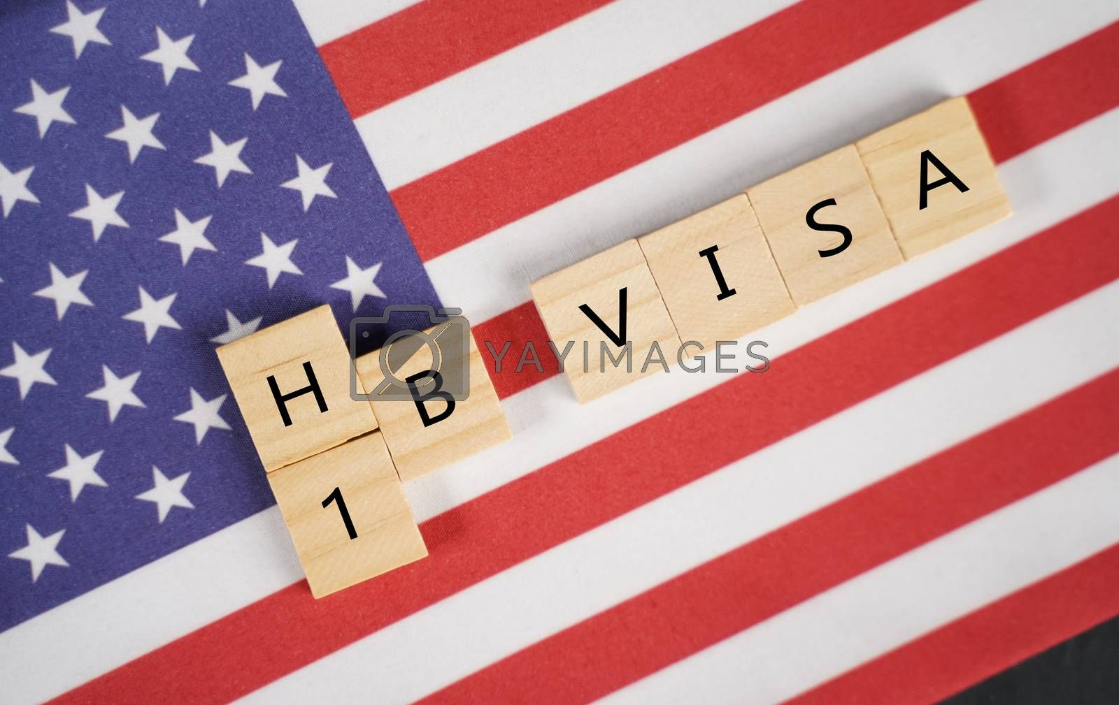 Concept of H1b Visa for foreign workers showing wooden letters with US or United states flag as background.