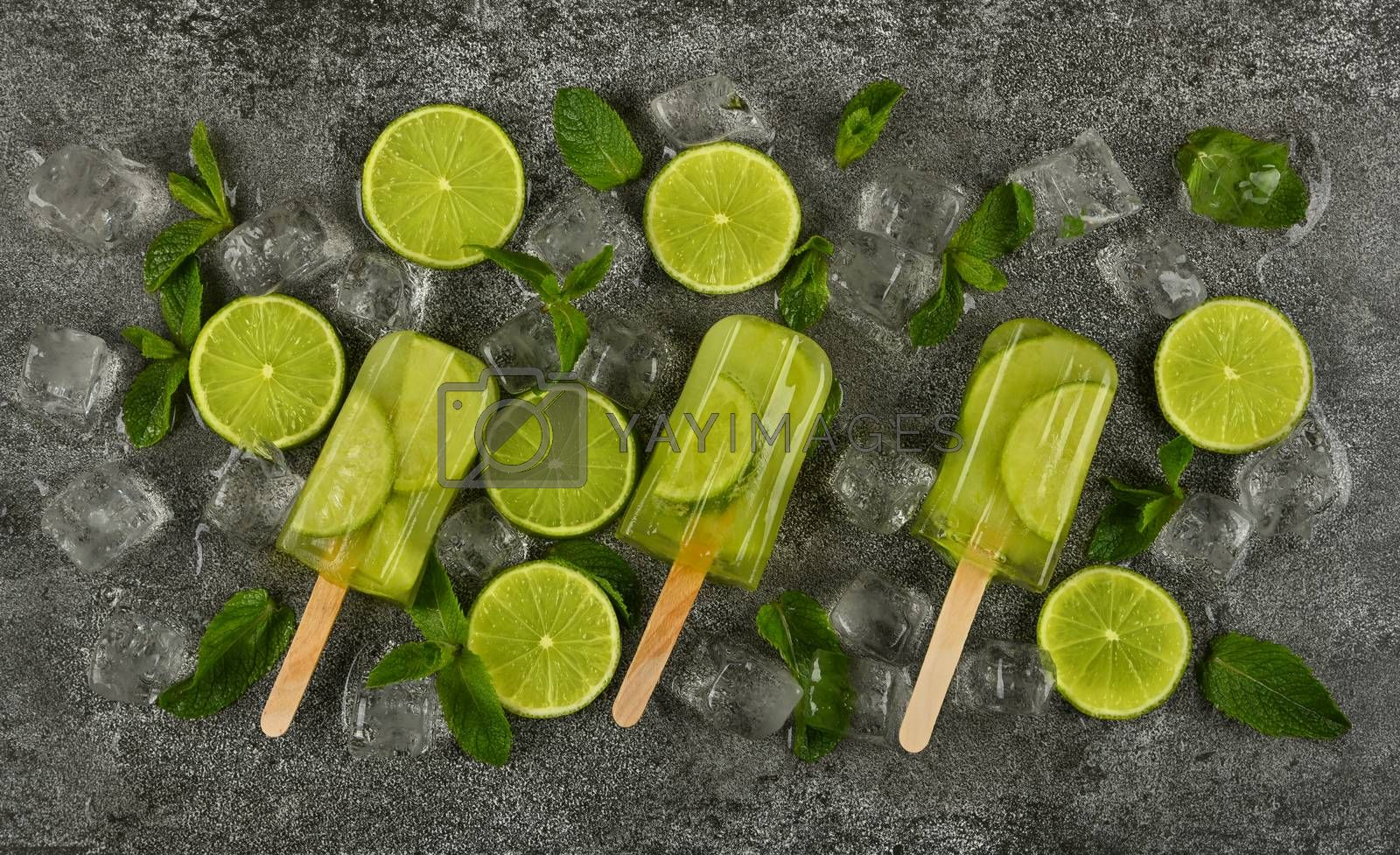 Close up several frozen fruit juice popsicles with fresh lime slices, green mint leaves and ice cubes on gray table surface, elevated top view, directly above