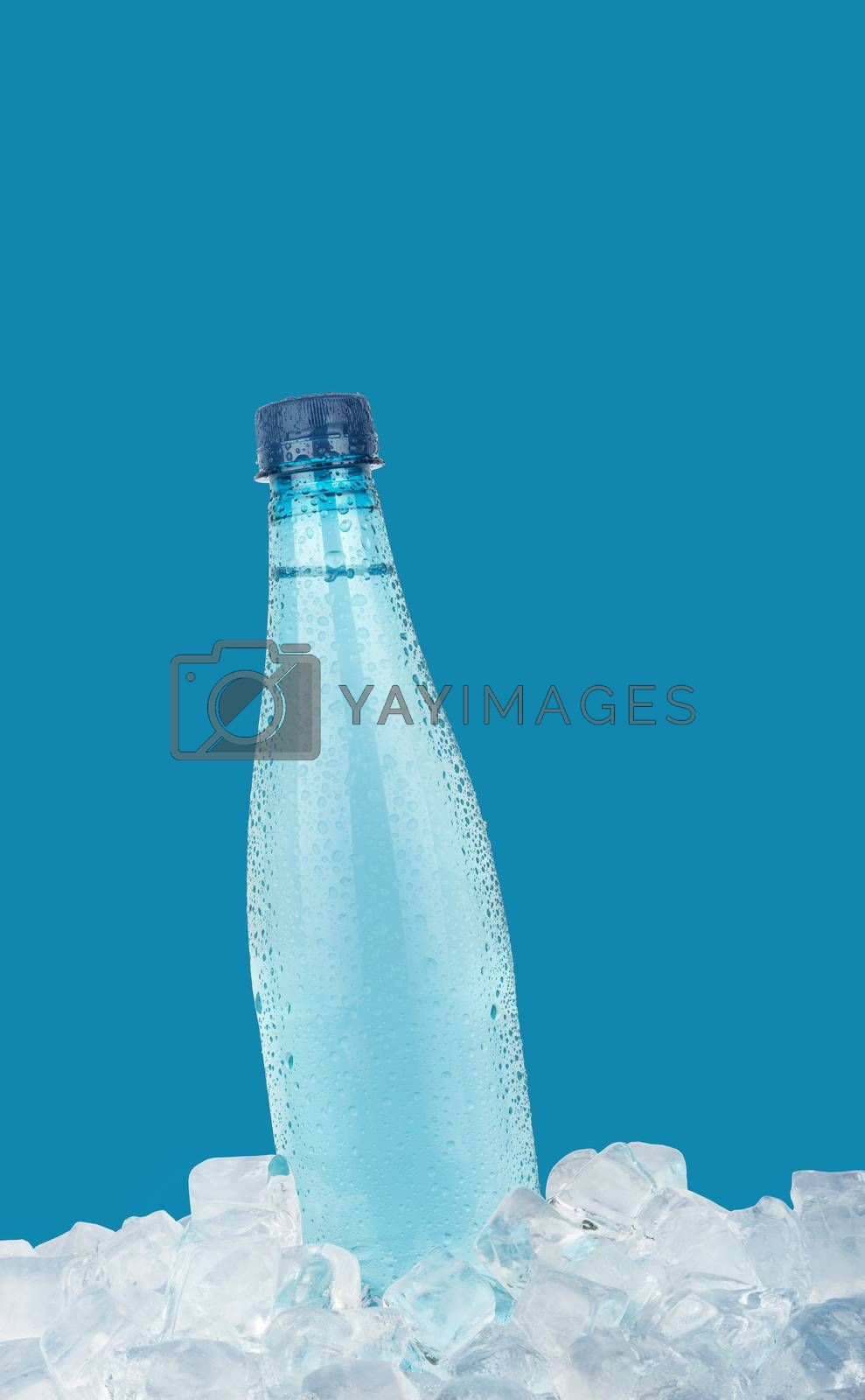 One full PET plastic bottle of cold still drinking water chilling on ice cubes isolated on blue background, low angle side view