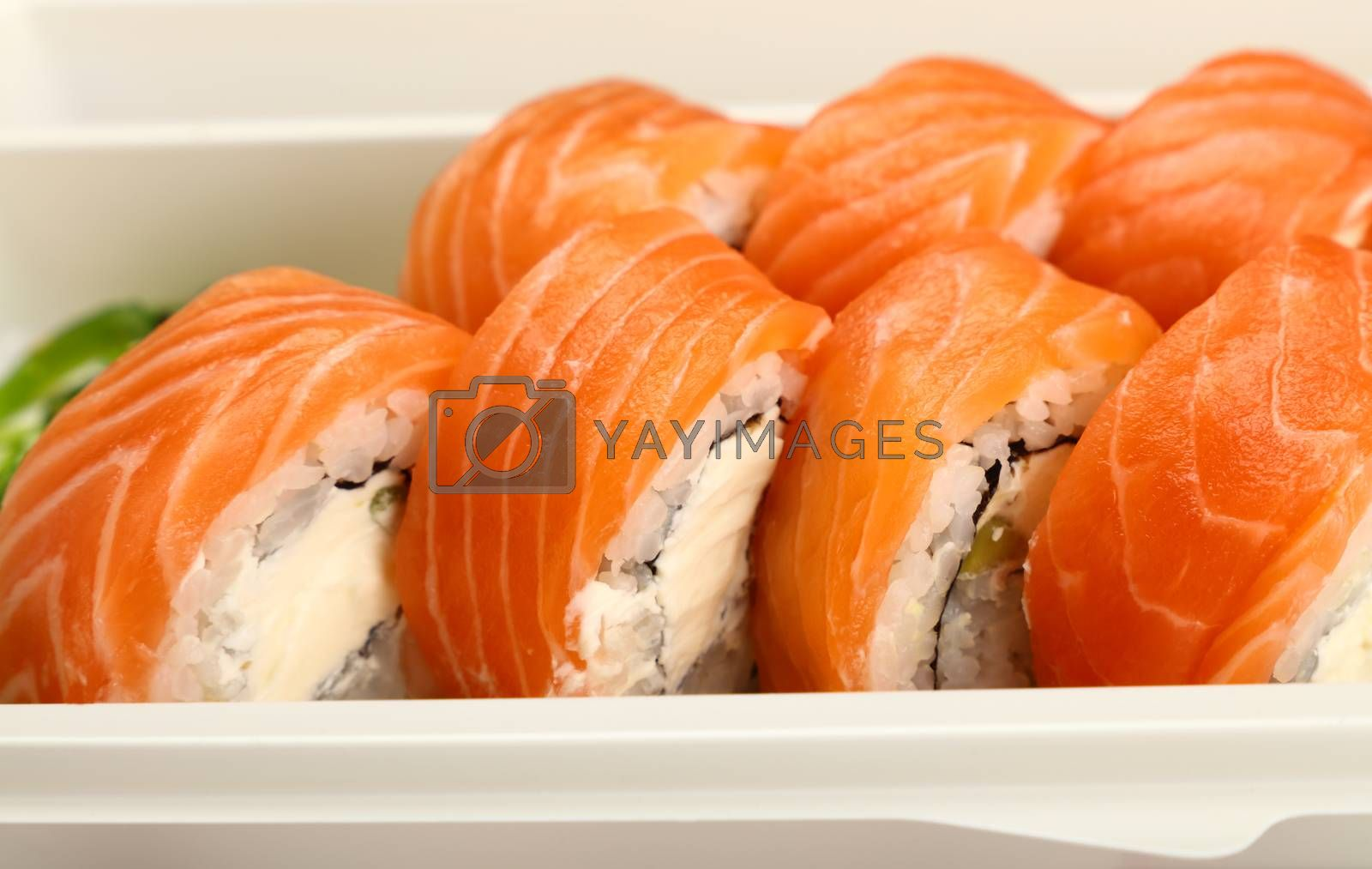 Close up take away set of six Philadelphia sushi rolls with raw salmon in disposable plastic tray, high angle view