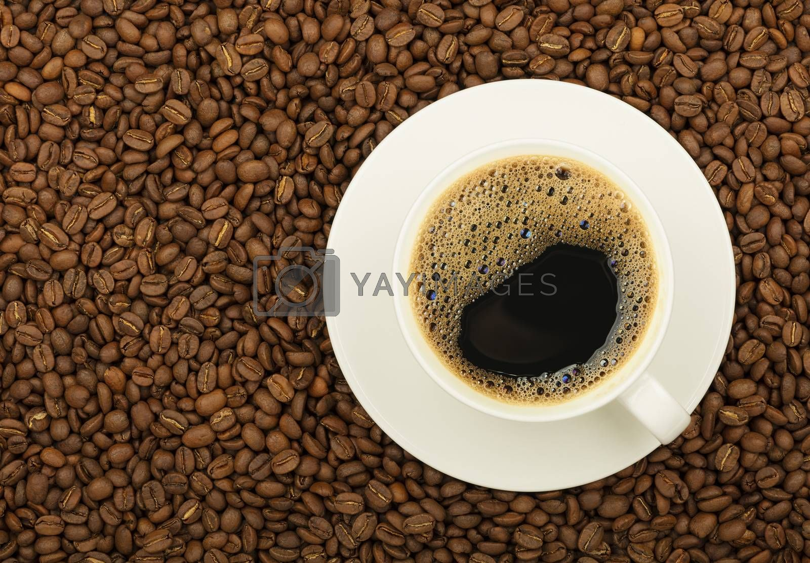 Close up white cup on saucer full of black coffee over background of roasted coffee beans, elevated top view, directly above