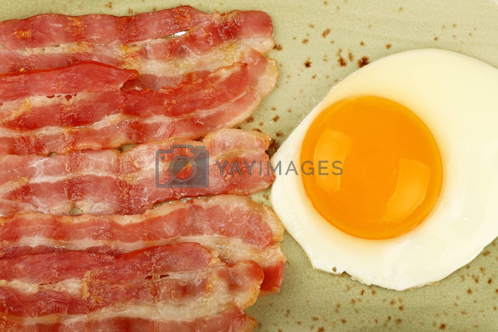 Close up English breakfast, sunny side egg and roasted bacon slices on blue plate, elevated top view, directly above