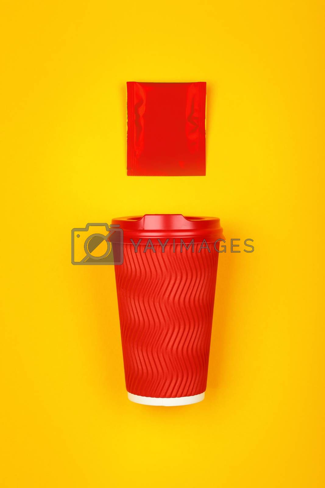 Close up one crimped disposable red paper takeaway cup and instant coffee, sugar or teabag sachet over vivid yellow background, flat lay, elevated top view, directly above