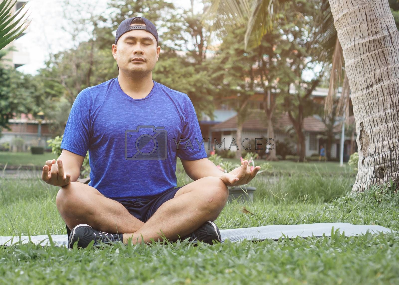 Sportsman meditate on the grass in the park. Young Asian men are healthy and fit to wear sportswear. Sit and relax with yoga  After exercise. fitness and sport  athletic body, balanced life, concept