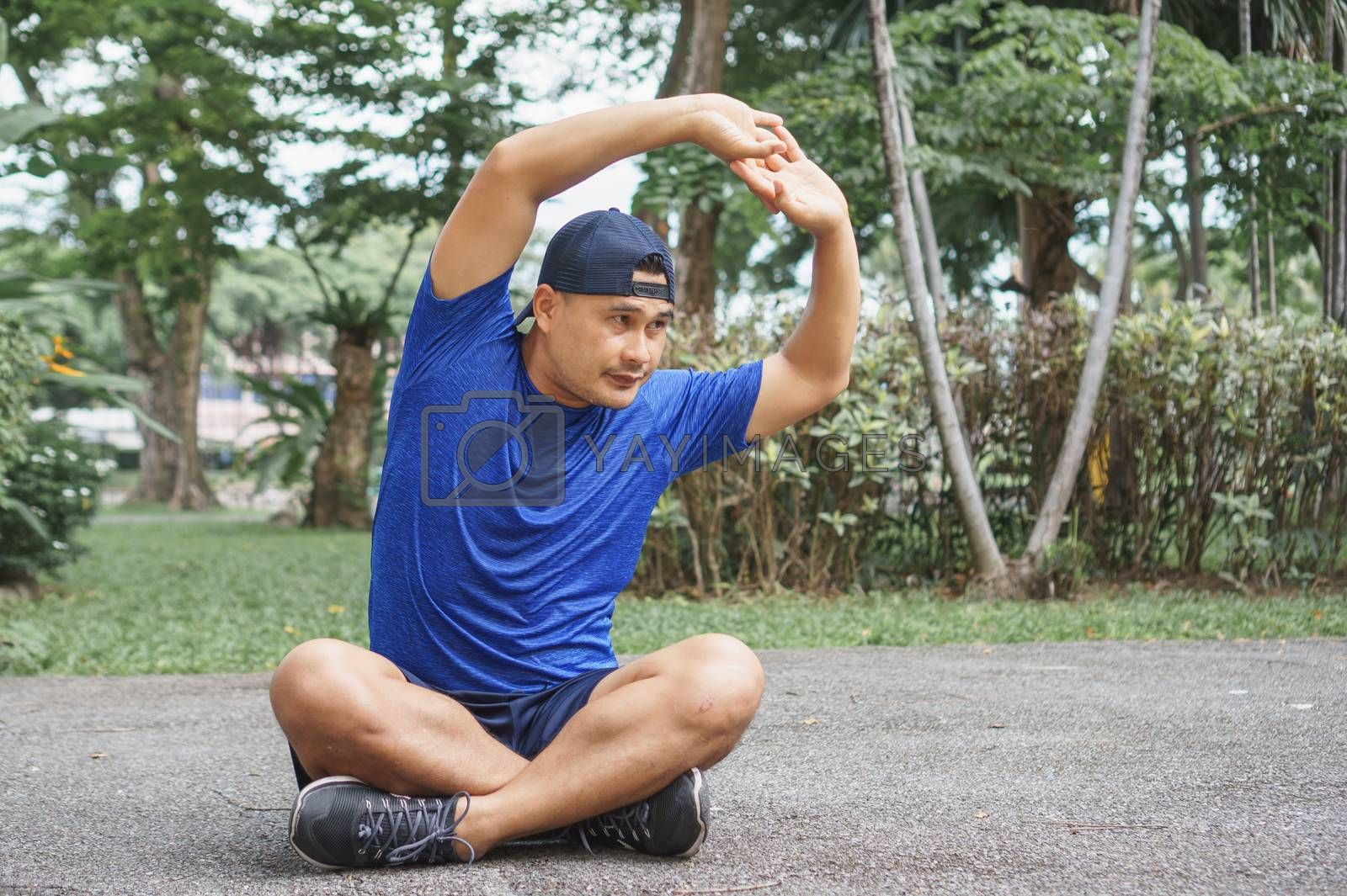Asian adult men, athletes wearing sportswear, are stretching with yoga postures in the park. Man runner sit and relax after exercise. sportsman fit, healthy body Strong and balanced life