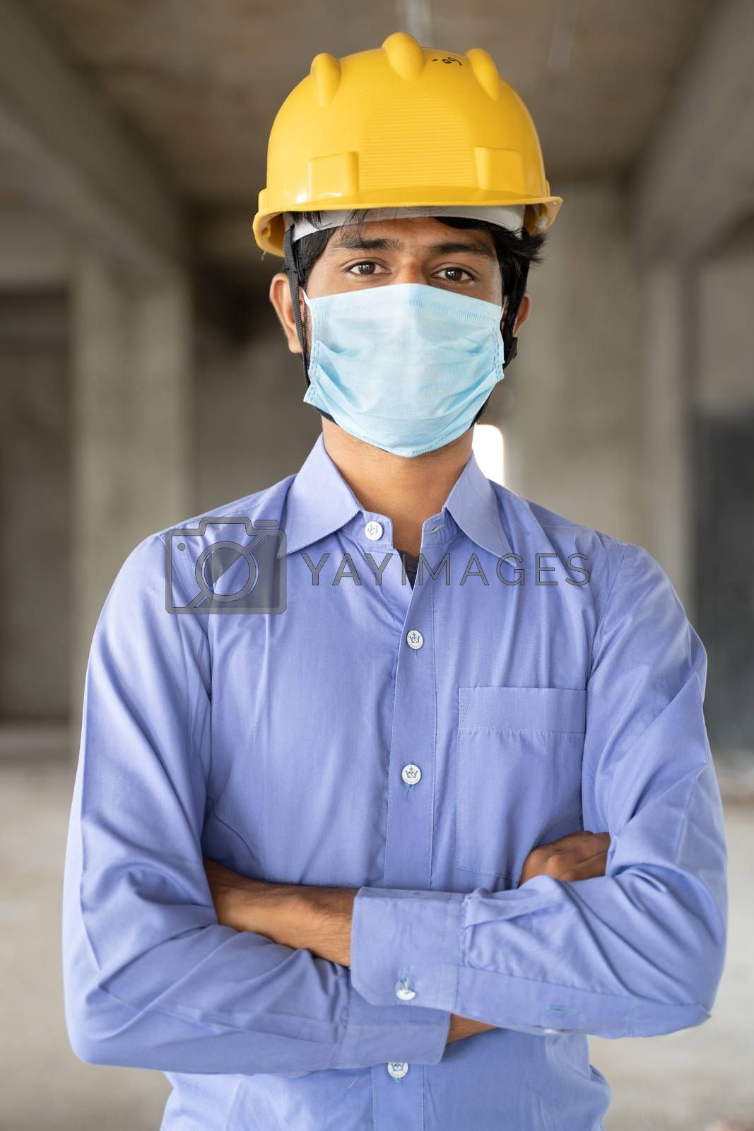 Concept of back to work, opening of construction sites - portrait of confident male construction worker in a construction helmet with medical mask due to coronavirus or covid-19 pandemic