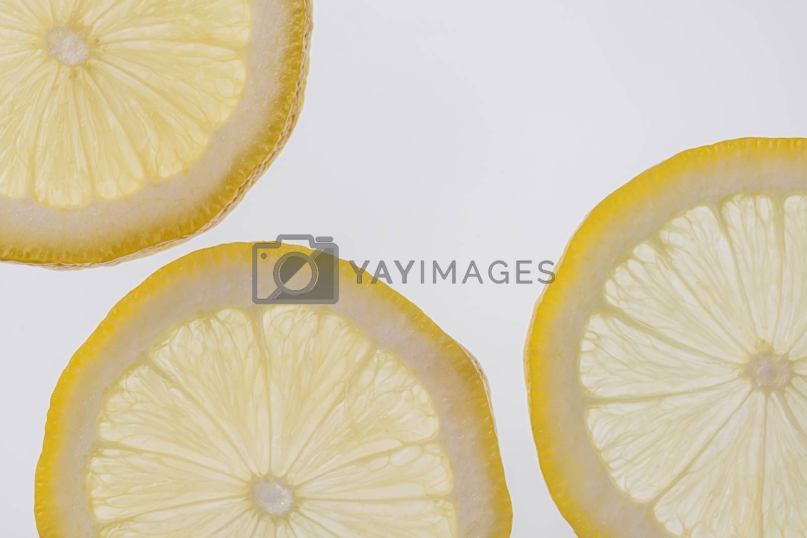 Fresh yellow lemon slices against a white isolated background