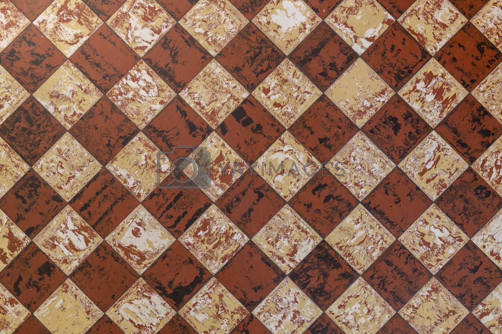 Old-fashioned antique brown beige floor tiles in a characteristic old farmhouse in the Netherlands as a full-screen background photo.