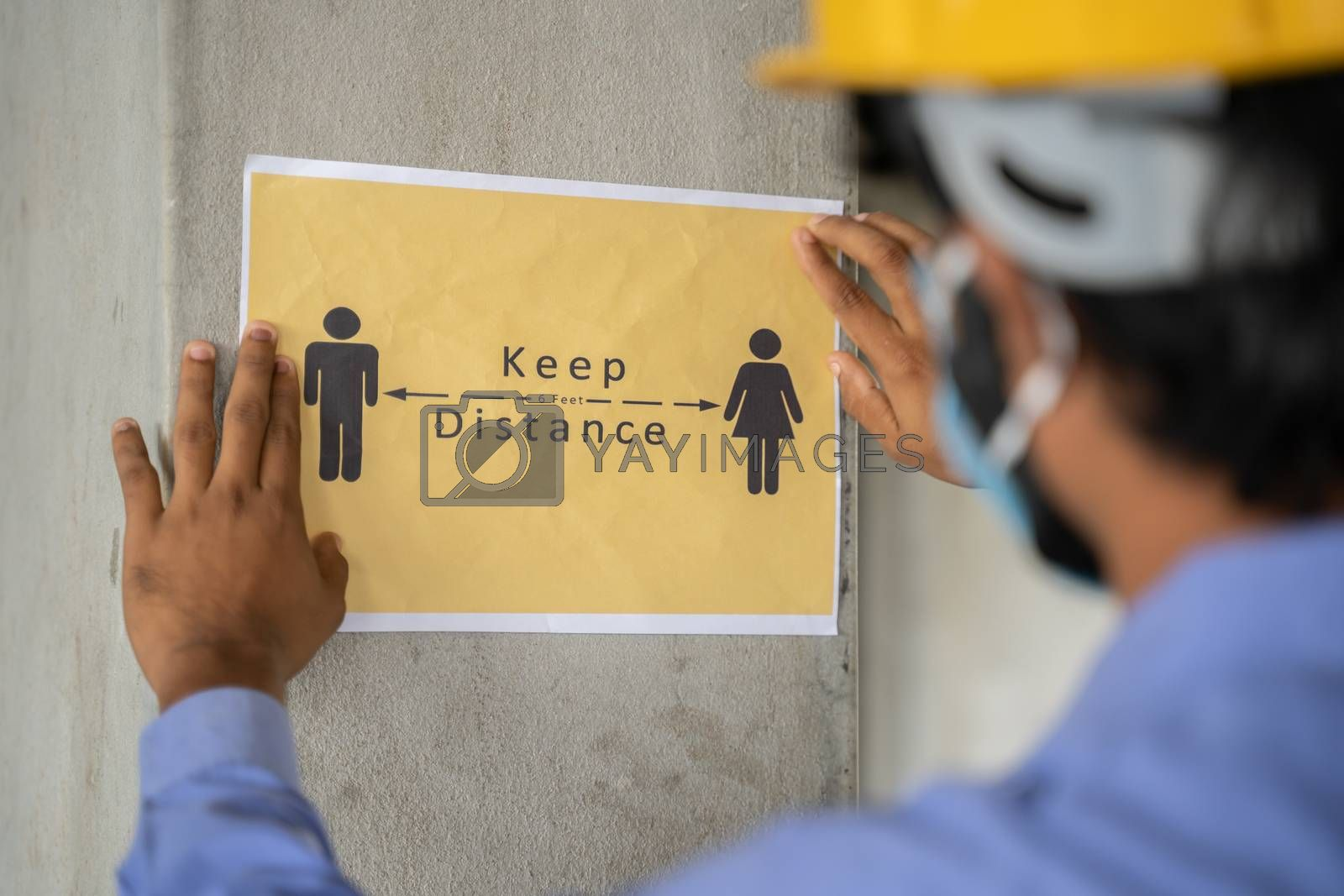 worker pasting Keep 6 feet distance on wall at work place or construction site due to coronavirus or covid-19 pandemic - concept of safety measures, back to work, new normal and protection