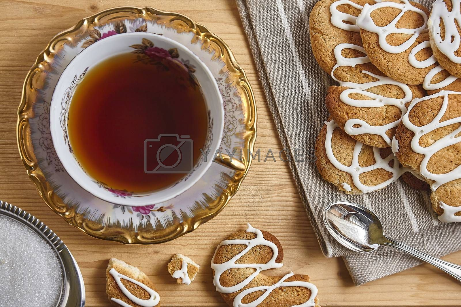 Combination of food with tea and biscuits on a wooden table from above