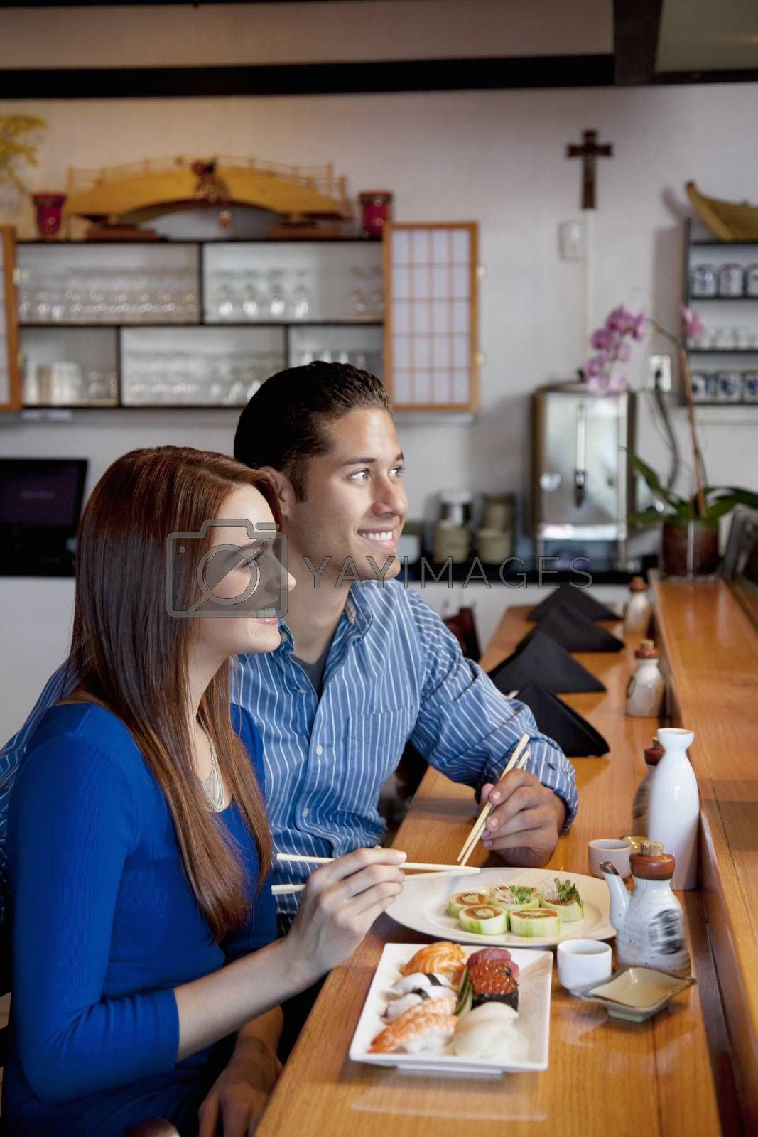 Portrait of a happy couple with Japanese cuisine