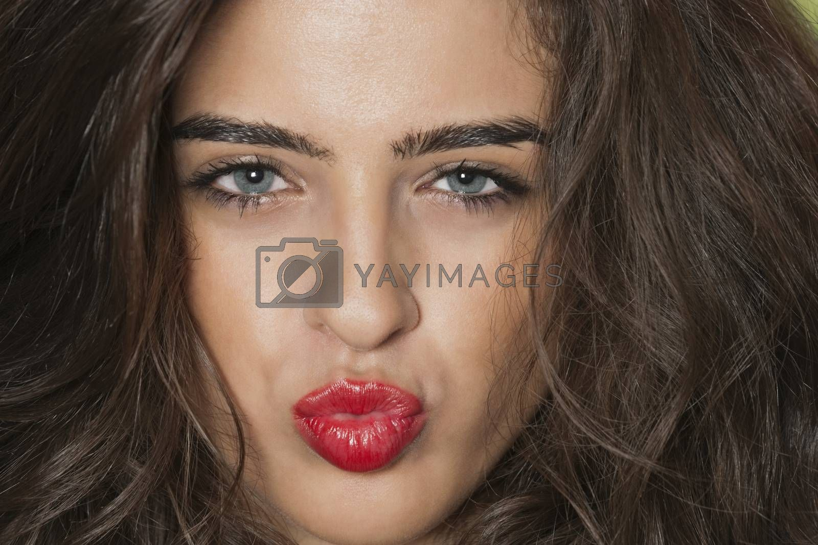 Close-up portrait of a seductive young female puckering lips