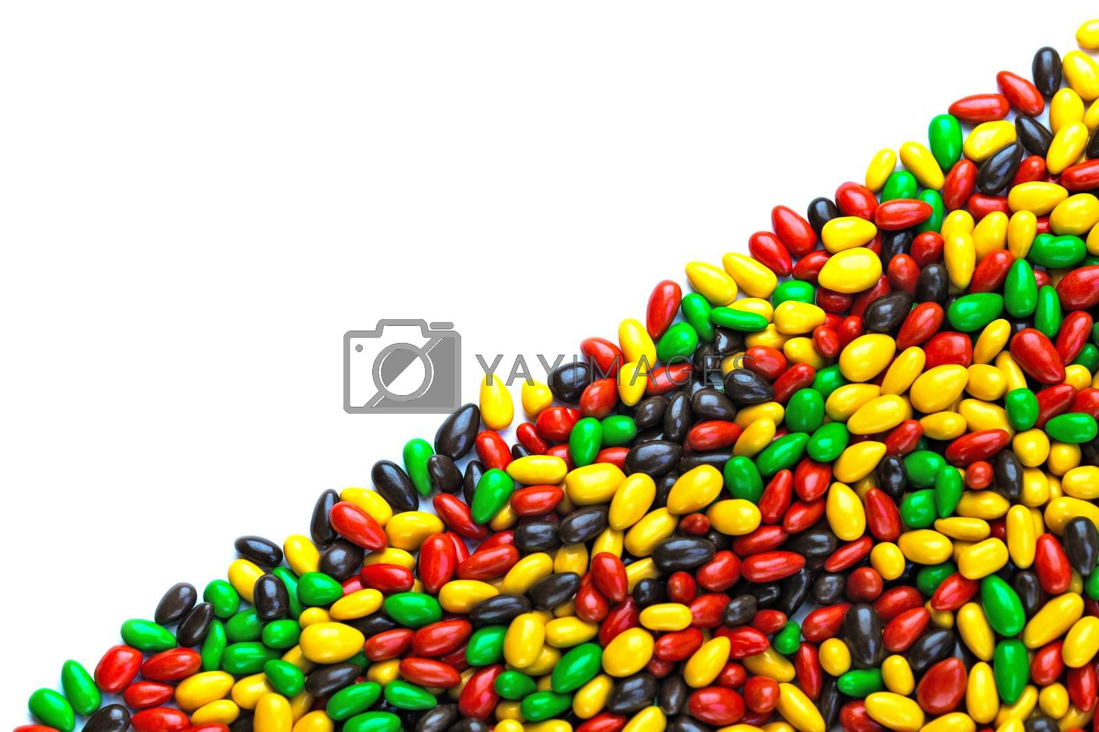 hundreds of small gloss glazed sunflower seeds multicolor flat background with selective focus with isolated side on white backgroud