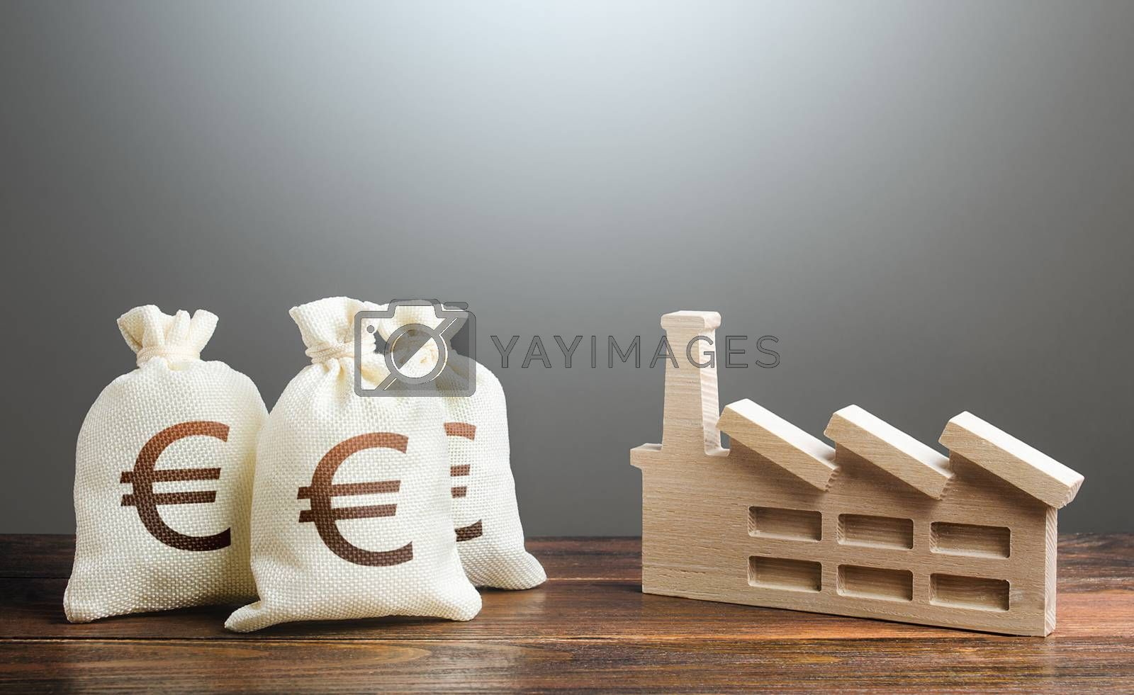 Euro money bags and industrial factory plant. Investment modernization, automation, reduction of the impact on environment. Privatization and purchase of industrial complexes. Supporting economy.