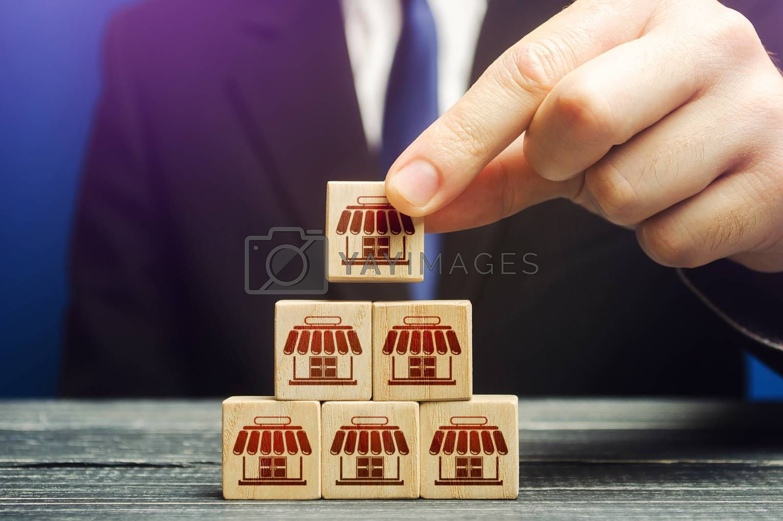 A man builds a pyramid from blocks of business shops. Building a successful business empire. Expansion and competitive growth. Franchise concession concept. Commercial network development.