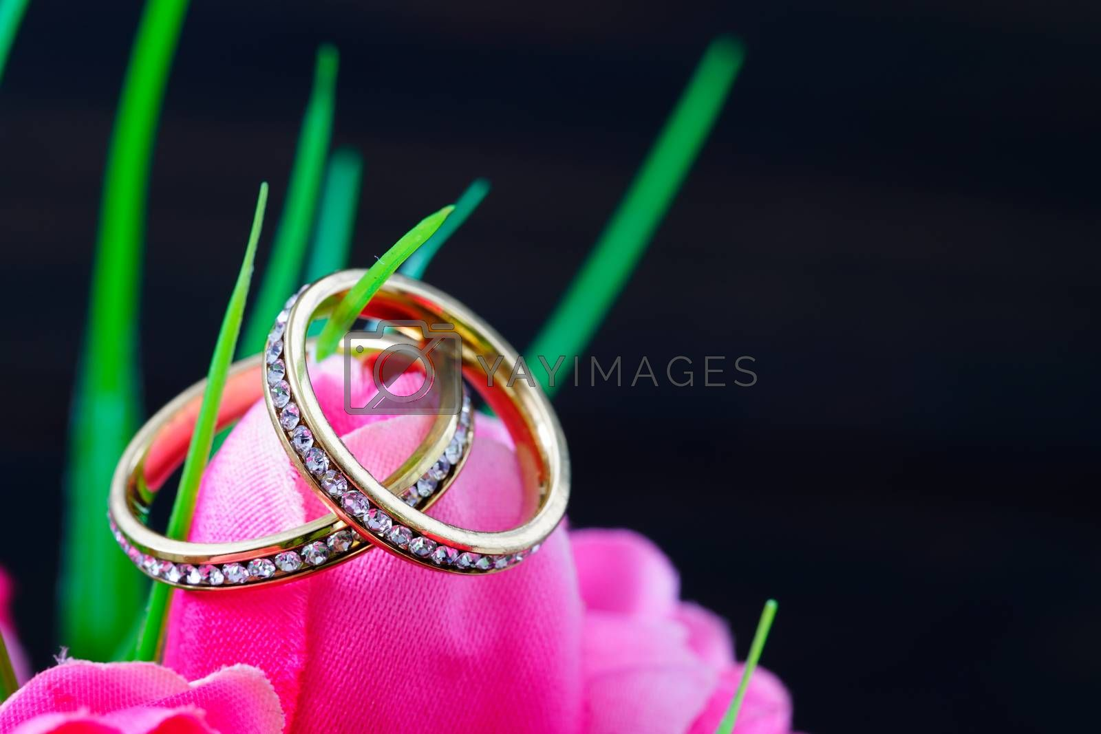 Wedding ring resting in a fake pink tulip flower by stoonn