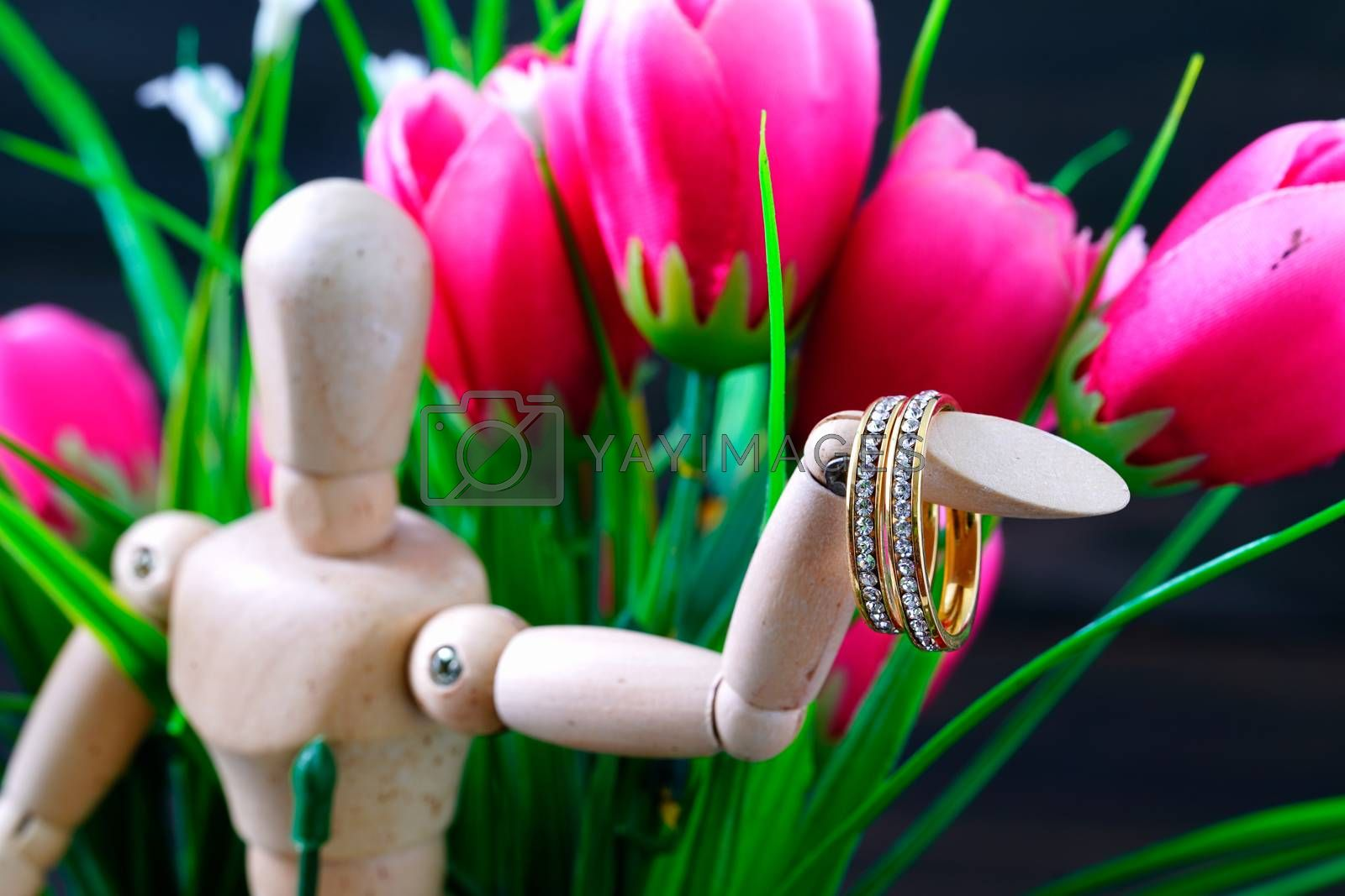 Wooden figure holding two golden wedding ring resting with fake pink tulip flower
