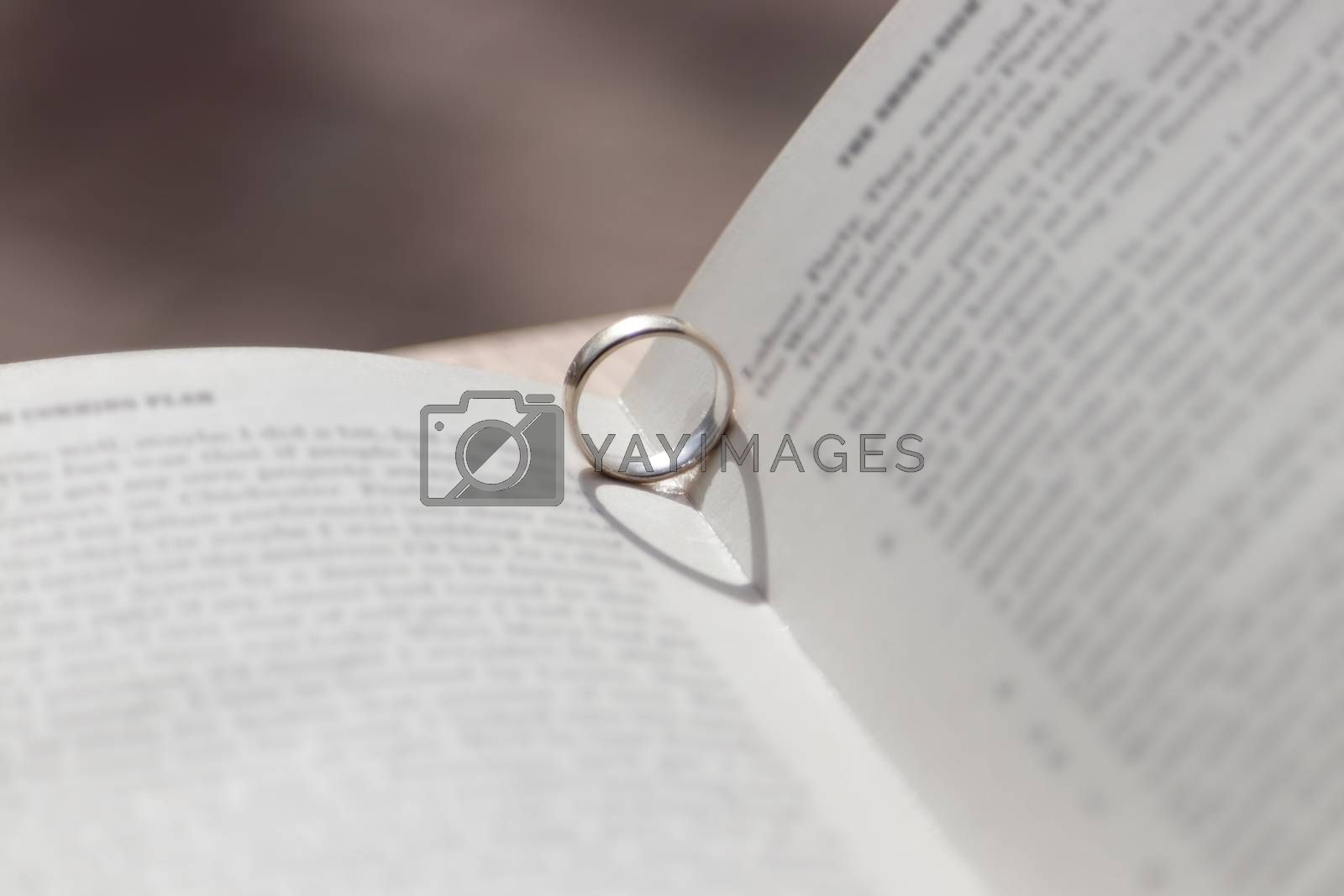 Romantic novel opened with ring giving heart shadow by antonyrobinson