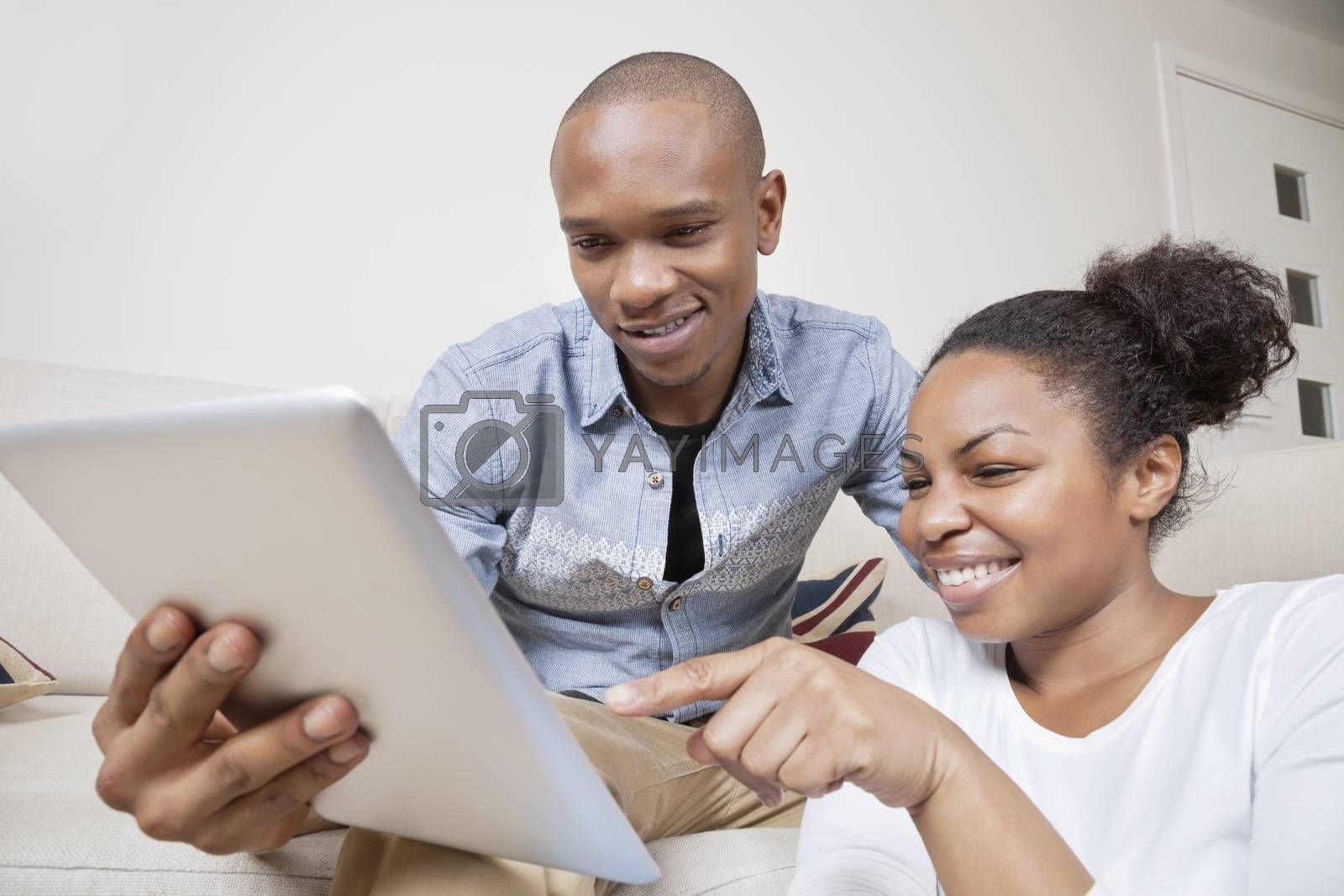 Happy African American young couple using digital tablet at home