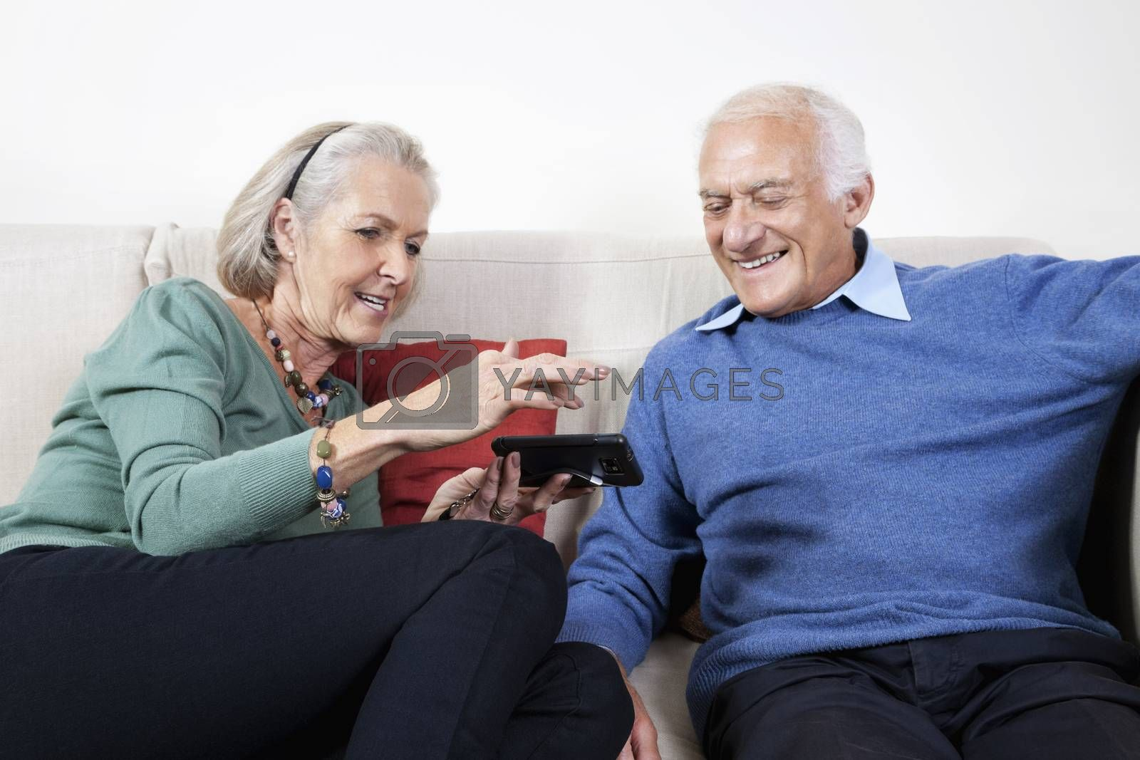 Happy senior couple using smart phone while sitting on sofa at home