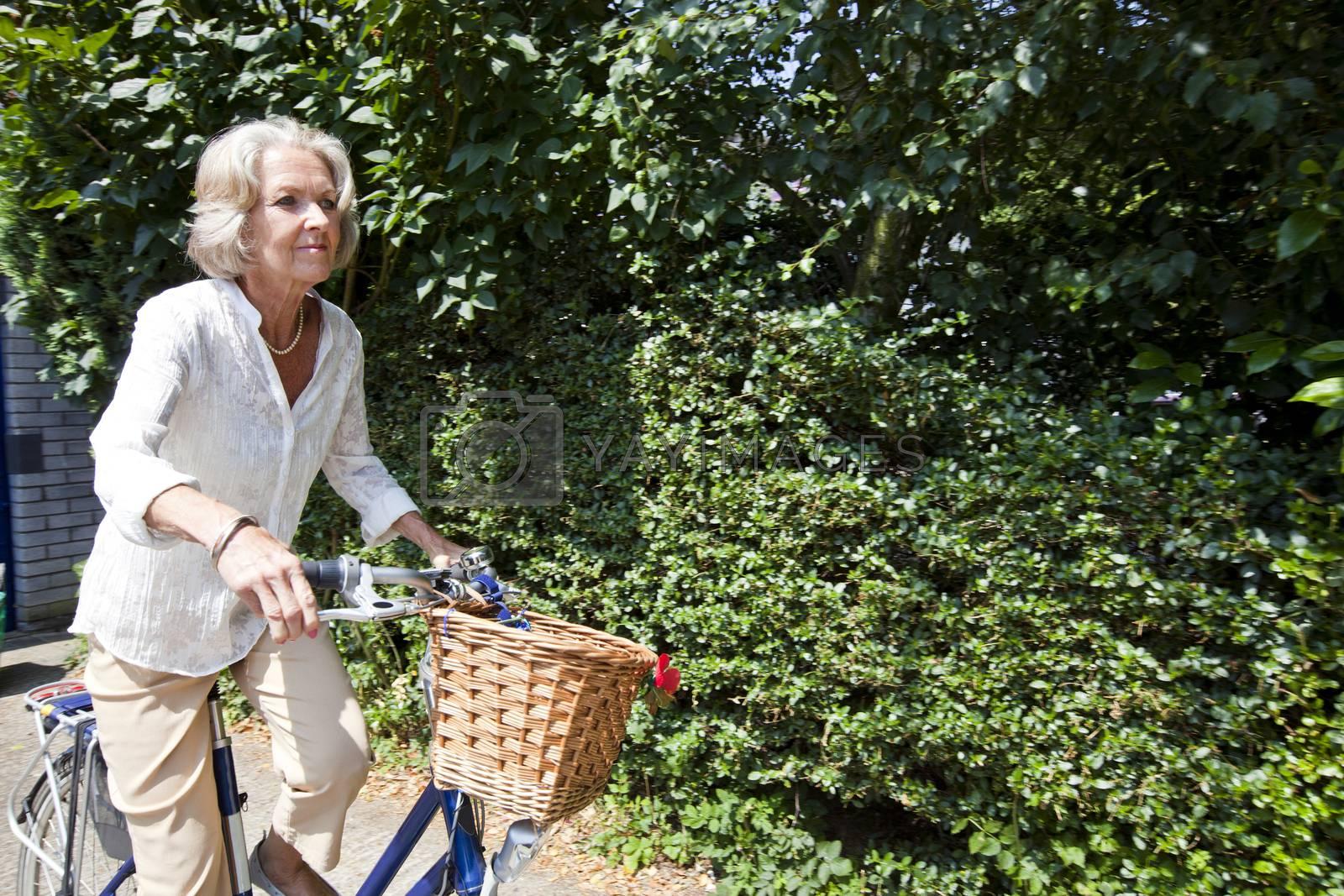 Active senior woman riding bicycle in backyard