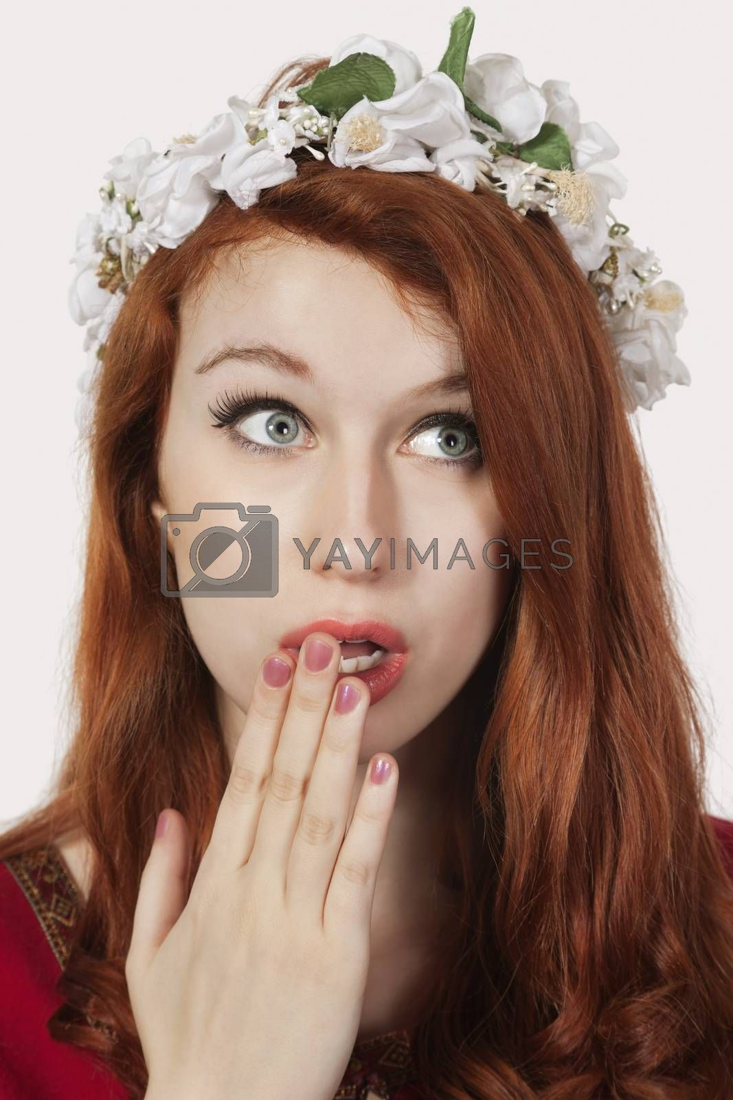 Shocked young woman in old-fashioned princess costume looking away against gray background