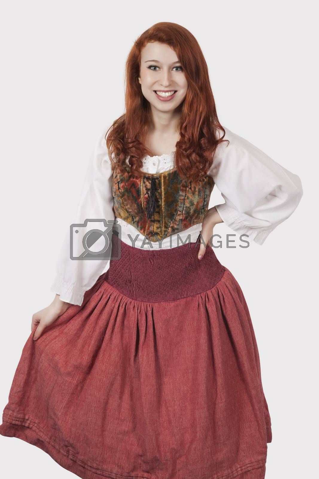 Portrait of young woman in old-fashioned costume standing against gray background