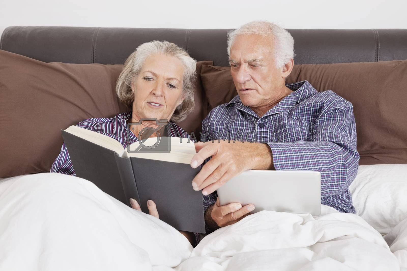 Senior couple with digital tablet reading book while lying on bed in room