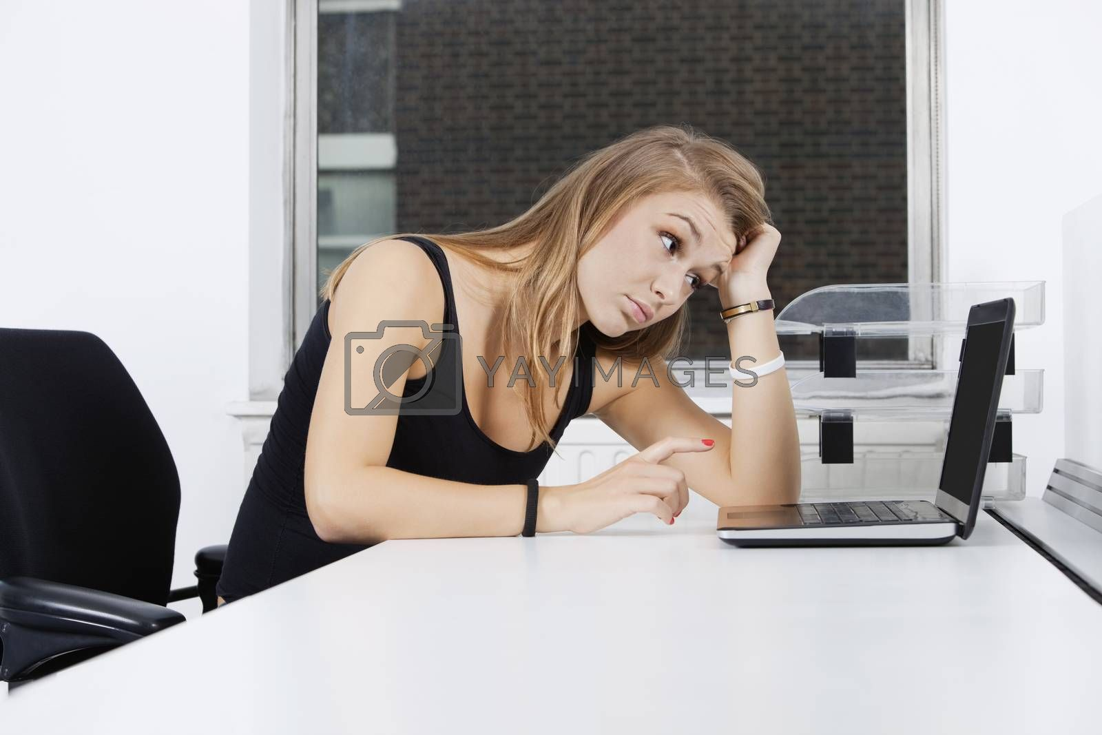 Tired young businesswoman looking at laptop in office