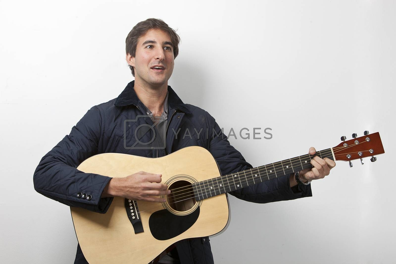 Young man playing guitar while signing against white background