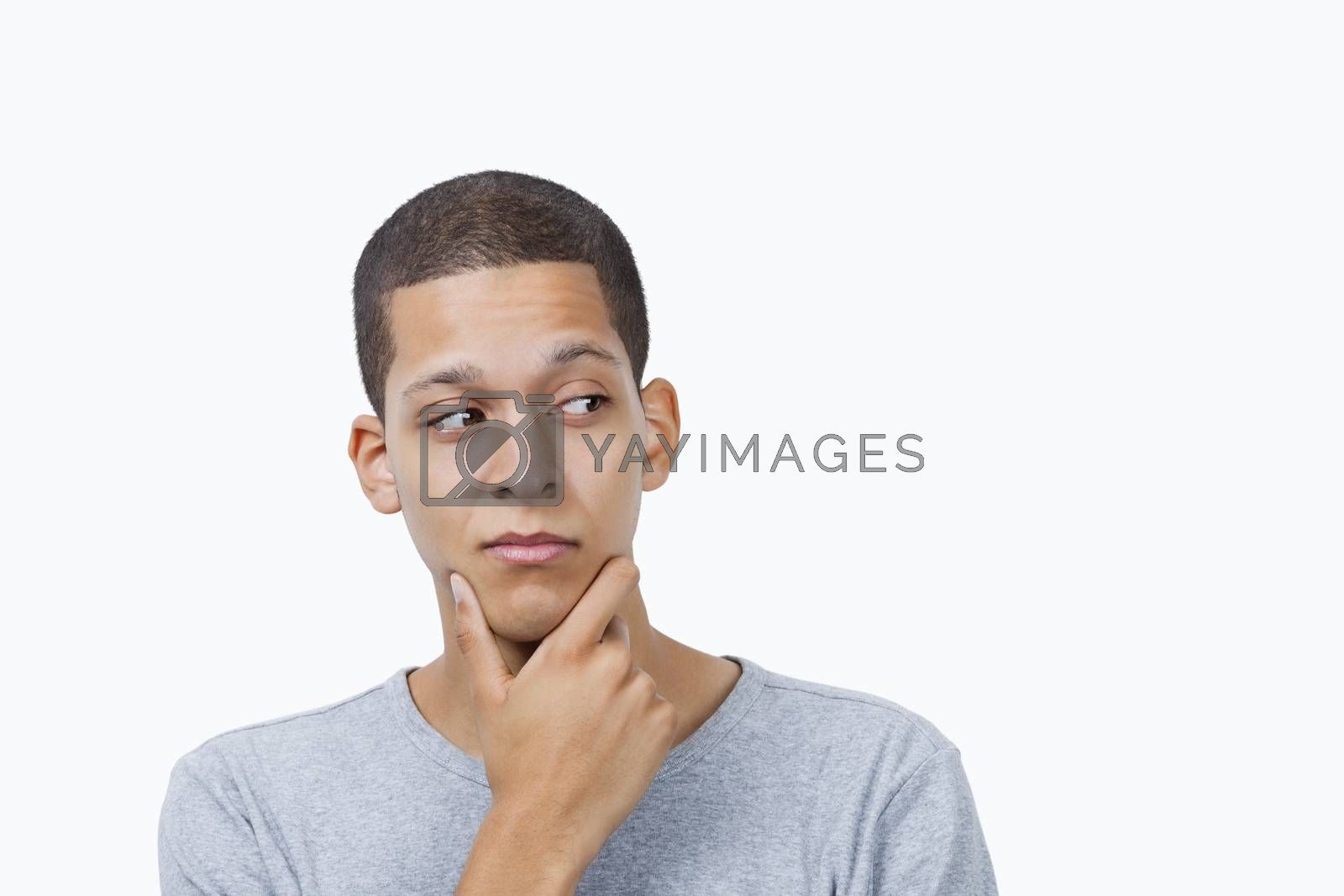 Confused young mixed race man with hand on chin against white background