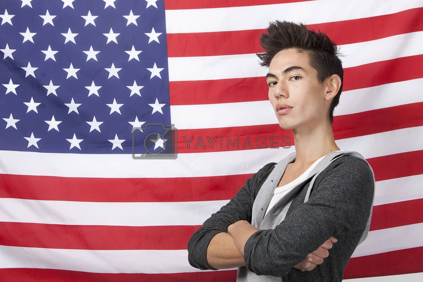 Portrait of young man with arms crossed standing against American flag