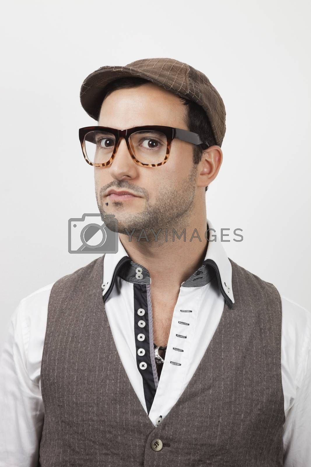 Portrait of young Caucasian man in flat cap against white background