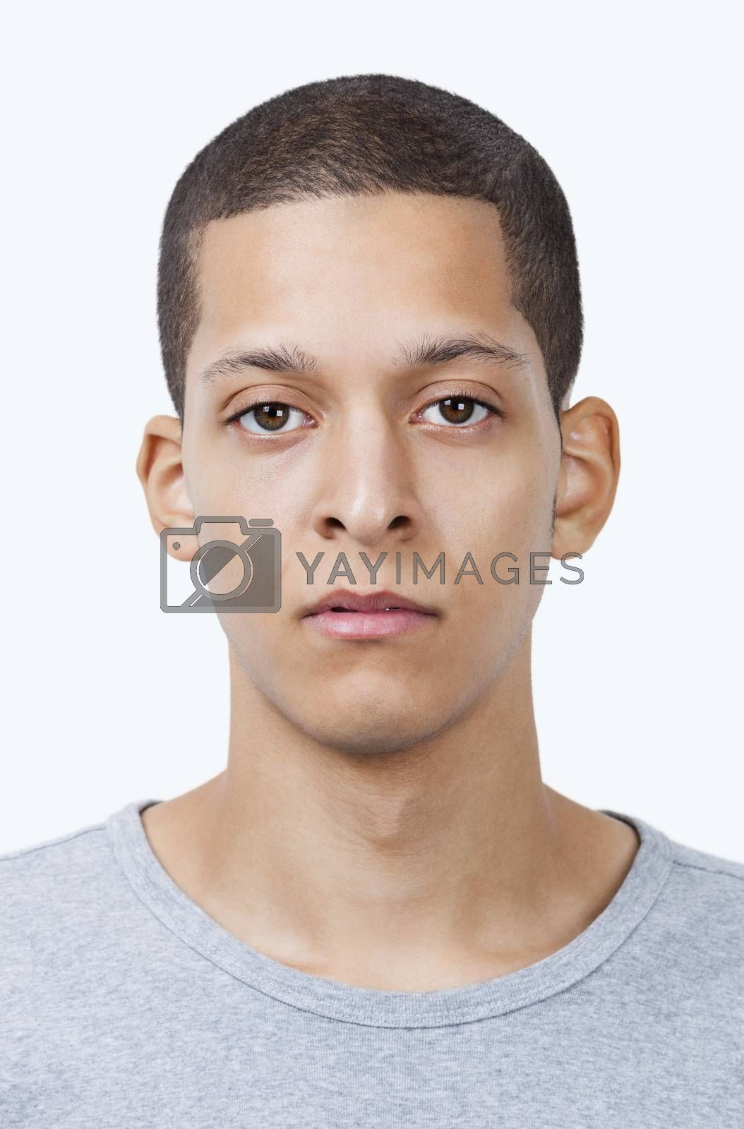 Portrait of young mixed race man against white background