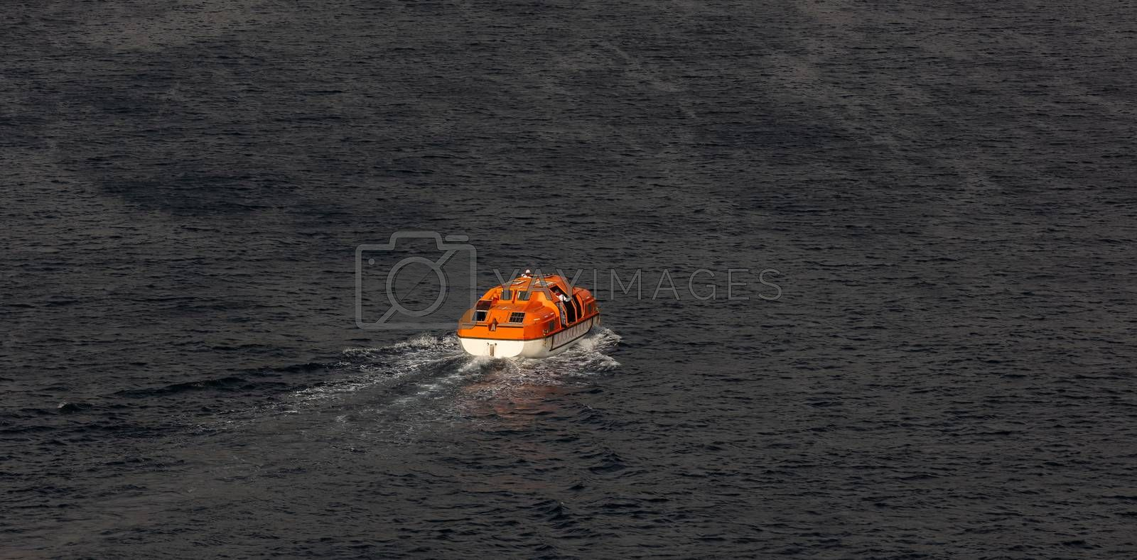 View of a single orange life boat with some seamen inside sailing at sea. Caribbean sea.