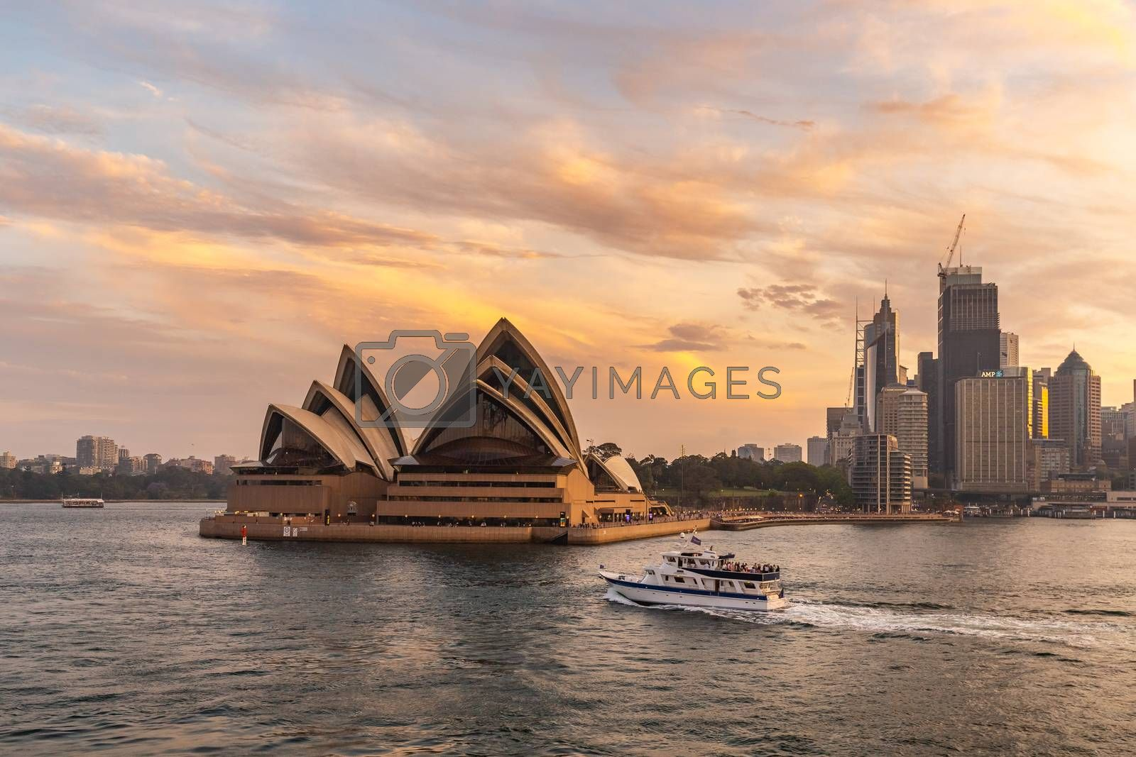 Sydney Harbor, Australia - November 1, 2018: Sydney Opera House at sunset. Beautiful orange-and-yellow colors. Down town and cloudy sky in the background. Tourist boat sailing the foreground.