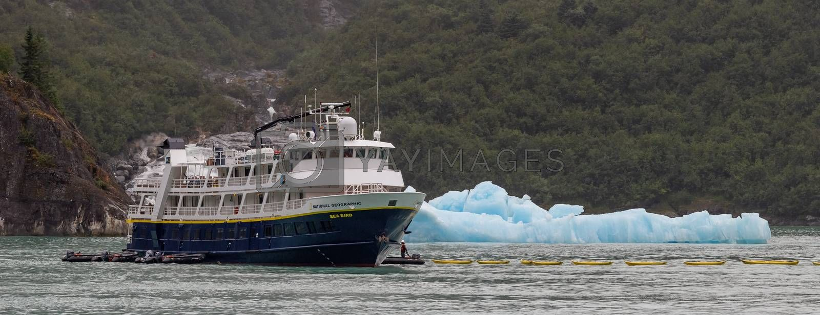 Tracy Arm Fjord, Alaska, US - August 23, 2018: National Geographic's Sea Bird vessel drifting by an iceberg with some personnel in a small boat next to it. Close view.