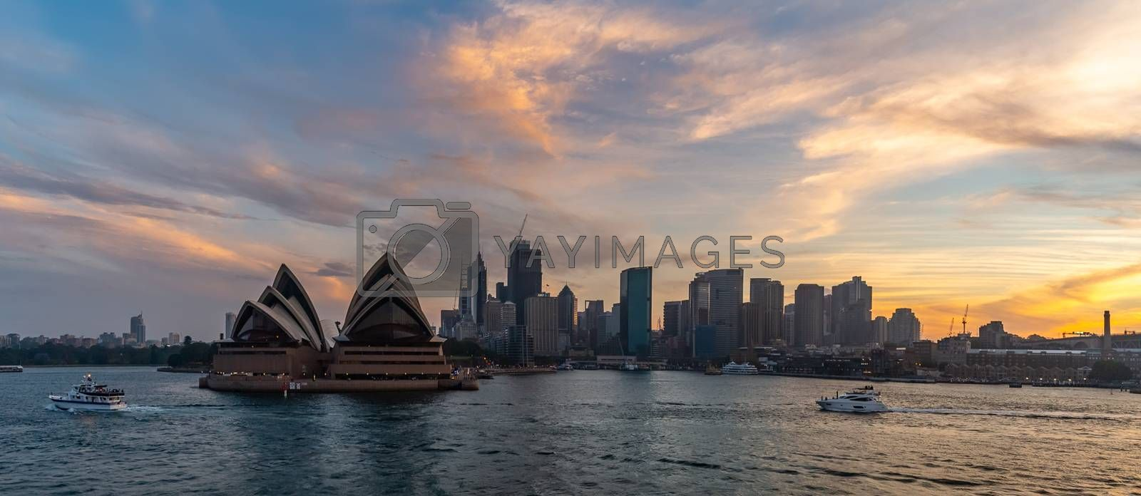 Sydney Harbor, Australia - November 1, 2018: Panorama. Sydney Opera House and downtown at sunset. Orange-and-yellow colors of the sky in the background. Tourist boats sailing in the foreground.