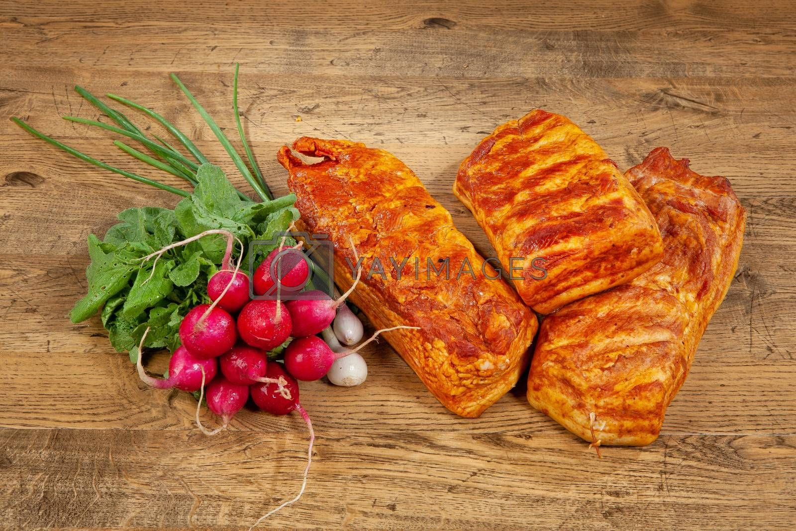 Ham sausage and radish on a wooden desk