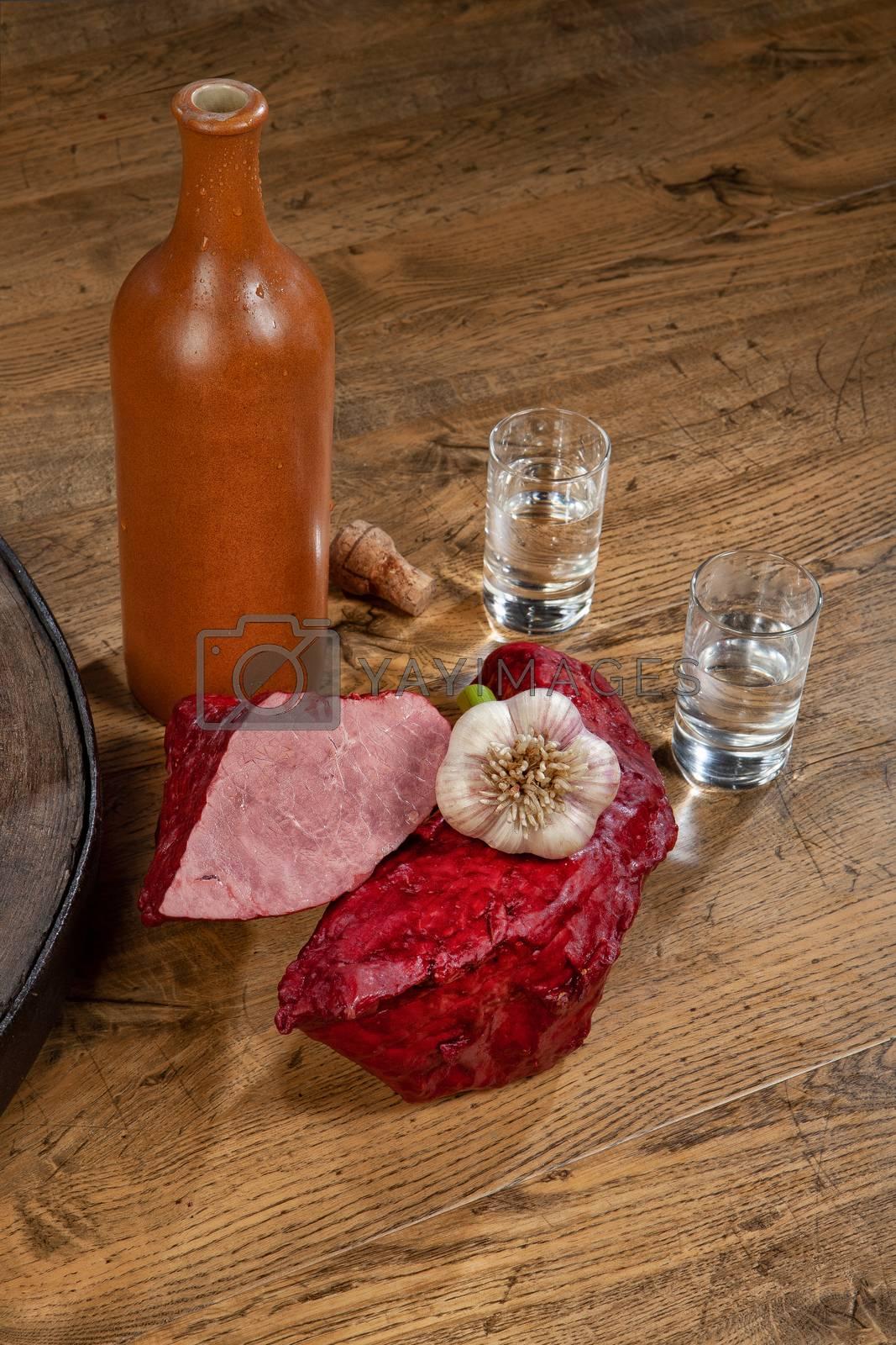Ham sausage, ceramic bottle and glasses of vodka on a wooden desk