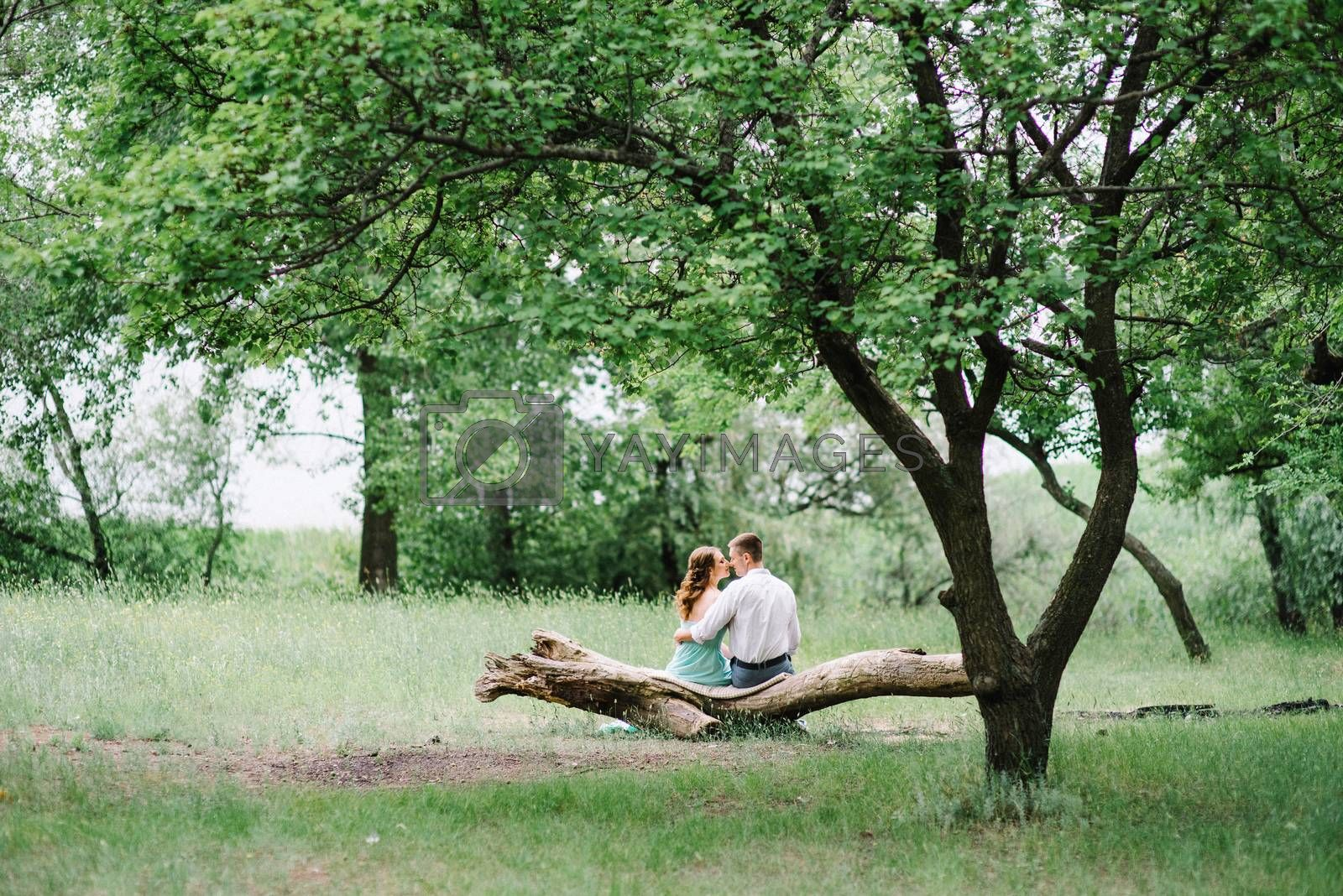 happy guy in a white shirt and a girl in a turquoise dress, the bride and groom are walking in the forest park