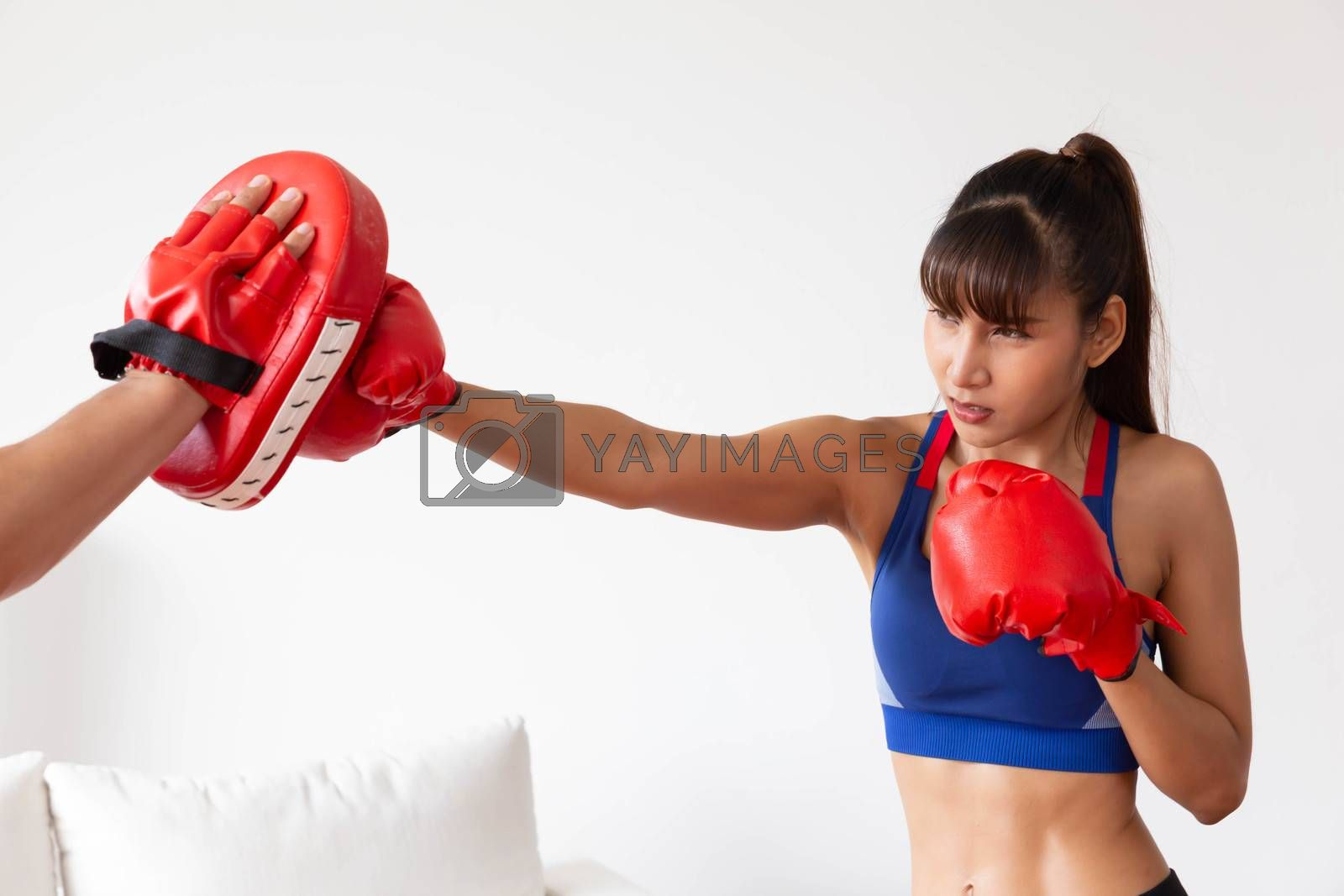 An asian women has boxing training with trainer by punch the target glove