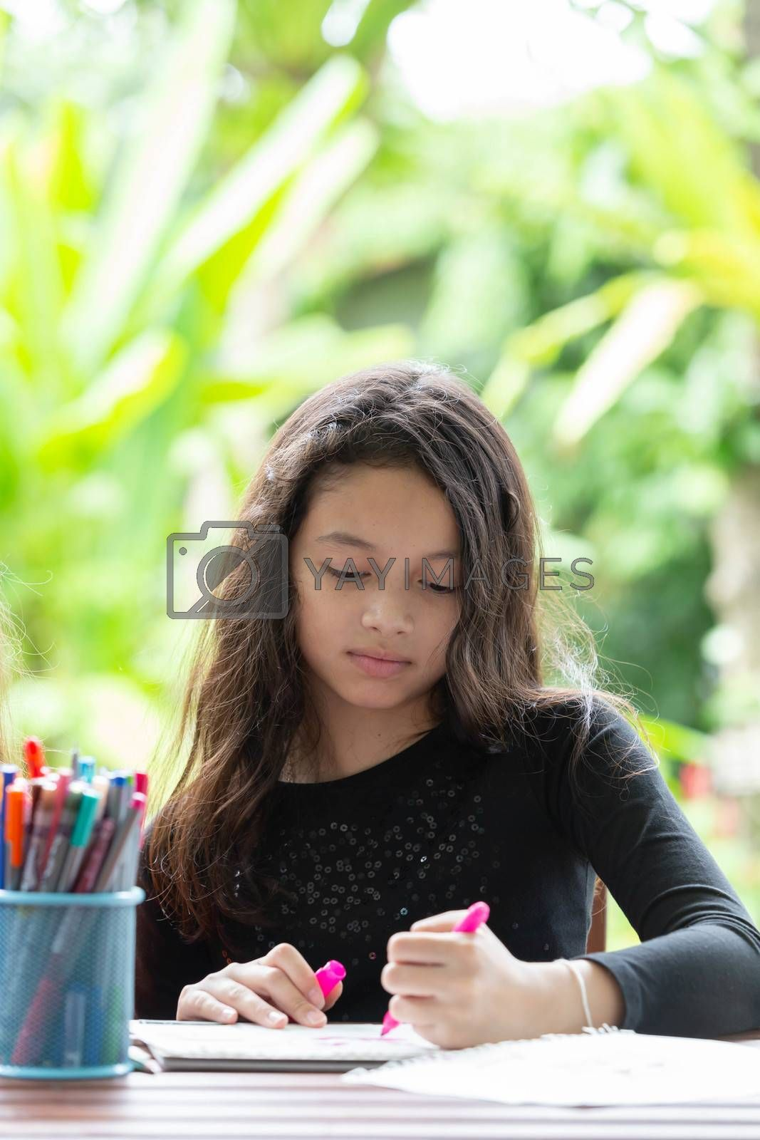 Cute girl doing her homework in the garden at home