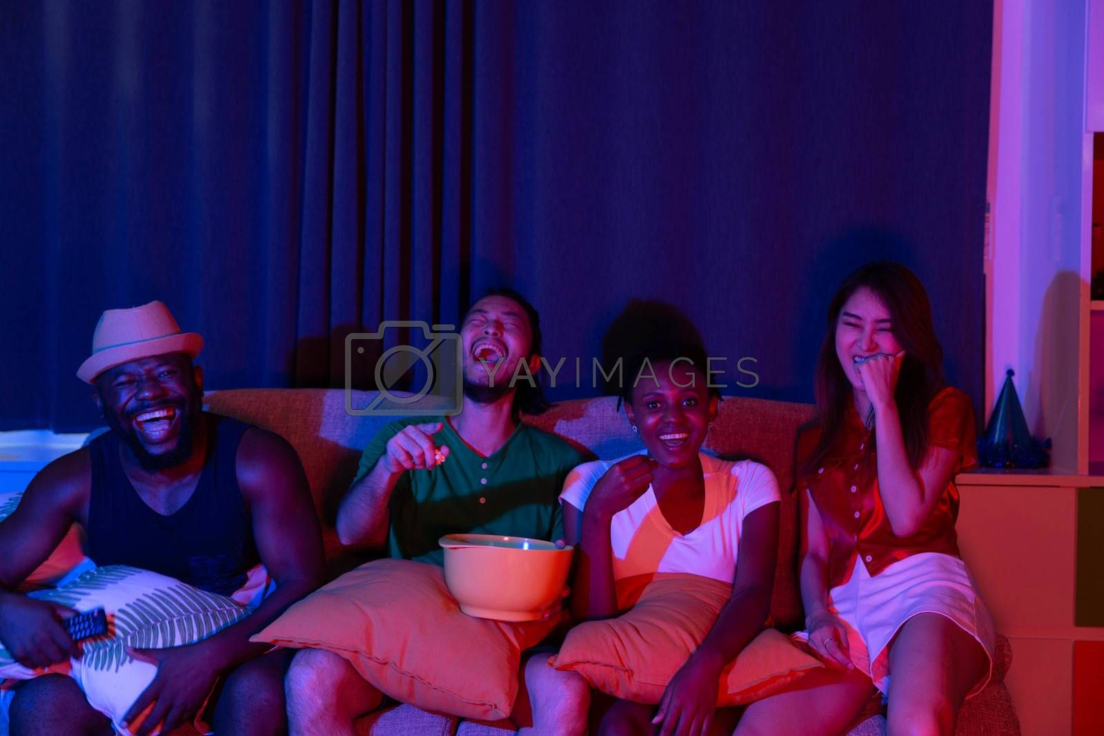 Friends laughing in sofa at home party under colorful light with drink and snack