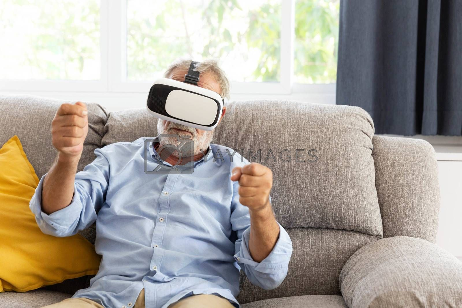 Senior retirement man playing with VR gadget in living room in his home