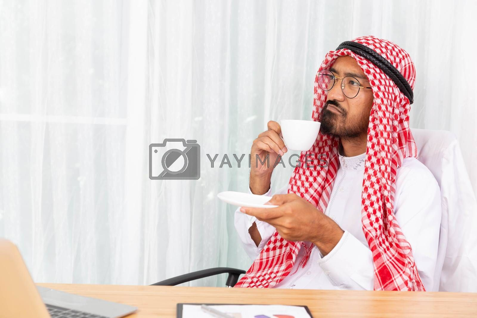 Arabian businessman is thinking about his work and having coffee in his office with computer notebook