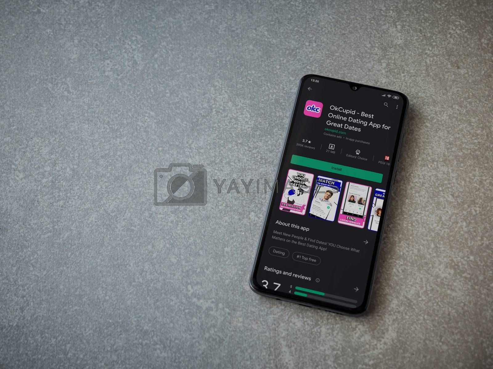 OkCupid app play store page on the display of a black mobile sma by wavemovies